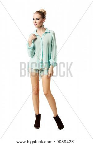 beautiful young woman wearing shorts and pastel blouse on white background