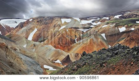 The famous Valley Landmannalaugar. Multicolored rhyolite mountains with the remnants of last year's snow. July in Iceland.