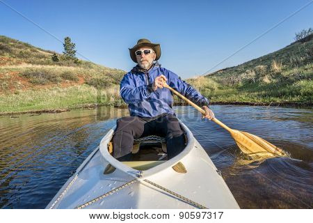 senior paddler in a decked expedition canoe on Horsetooth Reservoir, Fort Collins, Colorado, springtime scenery