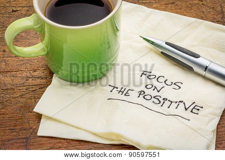 focus on the positive - motivational words handwritten on a napkin with a cup of espresso coffee