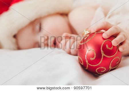 Small boy sleeping in a New Year's cap, focus on hand