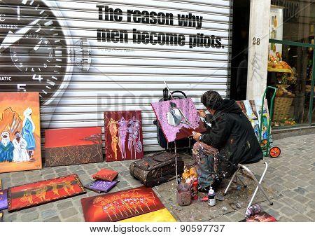 Street artist draws and sells paintings in Belgium
