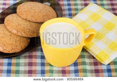 Round Brown Cookies In Black Dish And Cup Of Milk