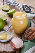 image of curd  - Jar of homemade lime curd with a spoon on old wooden background - JPG