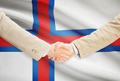 picture of faro  - Businessmen shaking hands with flag on background  - JPG