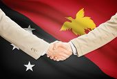 stock photo of guinea  - Businessmen shaking hands with flag on background  - JPG