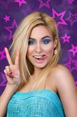 stock photo of tongue  - Portrait of young cheerful blonde woman showing her tongue and victory sign - JPG