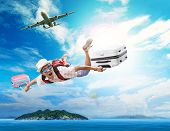 stock photo of crazy face  - young man flying from passenger plane to natural destination island on blue ocean with happiness face emotion use for people traveling on vacation holiday in summer season - JPG