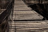 picture of suspension  - Old wooden suspension bridge with broken slats - JPG