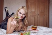 stock photo of hate  - Blonde woman hates salad laying on bed diet - JPG