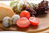 foto of quail egg  - quail eggs bread tomatoes and lettuce on a wooden cutting board - JPG