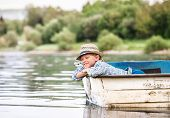 stock photo of life-boat  - Little Boy In Old Boat On The Calm Lake Surface - JPG