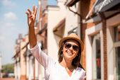 pic of waving  - Beautiful young woman in hat and glasses waving to someone and smiling while standing outdoors - JPG