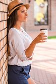 pic of funky  - Side view of thoughtful young woman in funky hat holding cup with hot drink and looking away while leaning at the wall outdoors - JPG