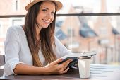 stock photo of funky  - Beautiful young woman in funky hat reading book and smiling while sitting outdoors - JPG