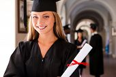 picture of graduation gown  - Happy young woman in graduation gowns holding diploma and smiling while her friends standing in the background