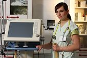 foto of icu  - Portrait female nurse in ICU in the green uniform with ventilator machine - JPG