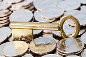 pic of golden coin  - Golden key on coins NOTE FOR INSPECTION: 66G is the weight of the key Business and finances conceptual image ** Note: Shallow depth of field - JPG
