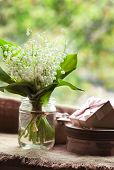 pic of lily  - Bunch of blooming lily of the valley flowers  in glass with water on rustic textile background - JPG