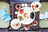 stock photo of breakfast  - Unfinished Turkish breakfast on a patio table with a serving of fried eggs with a selection of fresh tomato olives cheese and mugs of Turkish tea overhead view with napkins on chairs - JPG