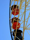 foto of amusement park rides  - ride a Ferris wheel at an amusement park against the blue sky - JPG
