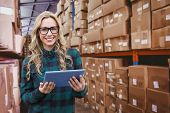 image of forklift driver  - Pretty blonde with tablet against forklift in large warehouse - JPG