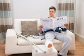 picture of crutch  - Disabled Man With Crutches Sitting On Sofa Reading Newspaper - JPG