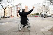 pic of disability  - Rear View Of A Disabled Man On Wheelchair With Hand Raised - JPG
