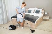 picture of housekeeper  - Female Housekeeper Cleaning Rug With Vacuum Cleaner In Hotel Room - JPG