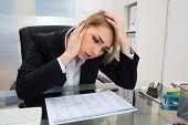 stock photo of employee month  - Portrait Of Stressed Businesswoman Sitting At Desk With Gantt Progress Chart - JPG