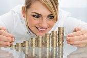 image of golden coin  - Young Happy Businesswoman Putting Coin On Stack Of Golden Coins - JPG