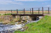 stock photo of old bridge  - Old pedestrian bridge over small Ukrainian river Kilchen  - JPG