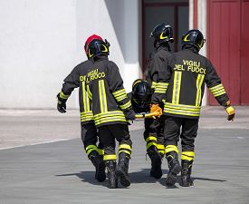 image of firefighter  - Four brave Firefighters carry a fellow firefighter with the stretcher - JPG