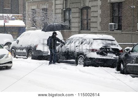 Man Cleans Car During Snow Storm