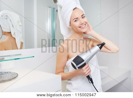 Woman  in the bathroom with hairdryer in hand