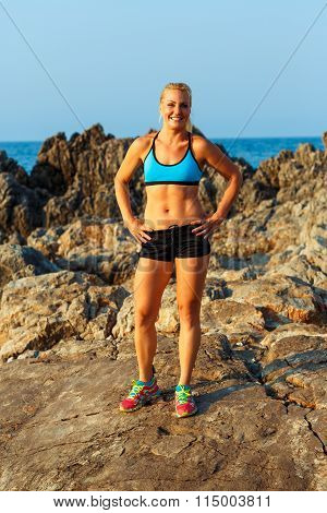 Athlete Woman Standing After Sport Exercising On The Rocks By The Sea
