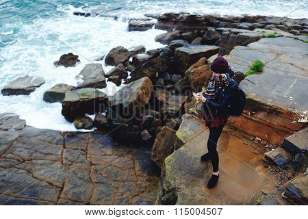 Young stylish hipster girl watching video on cell telephone during rest near ocean