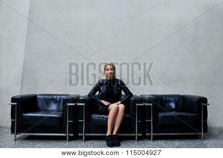 Charming stylish female waiting for someone in hallway of modern studio
