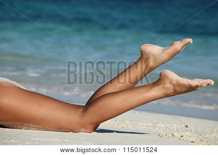 Beautiful tan female legs on sea beach