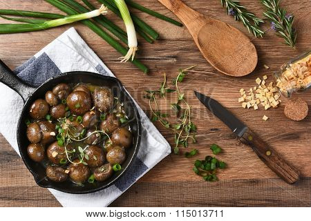 high angle view of sauteed mushrooms in a cast iron skillet surrounded by ingredients and utensils. Horizontal on a rustic kitchen table.