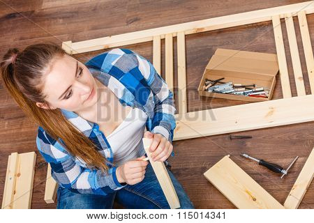 Woman With Screwdriver Nails Assembling Furniture.