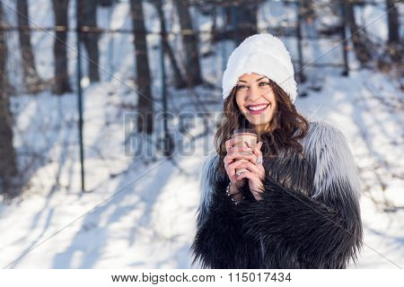 Cheerful young woman with takeaway coffee in winter in park
