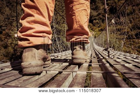Closeup of boots standing on a suspension bridge.