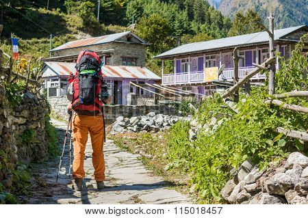 Hiker passing a village.