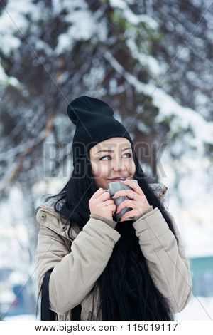 Young woman in park in winter drinking warm tea or coffee