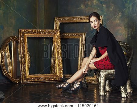 beauty rich brunette woman in luxury interior near empty frames, vintage elegance, gold close up roo