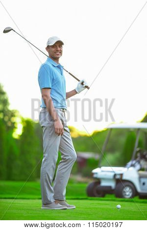 Man with golf clubs outdoors
