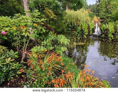 Small fountain in a quiet pond. Autumn day in the park. Butchart Gardens on Vancouver Island, Canada
