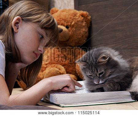 Cat and girl reading the book together