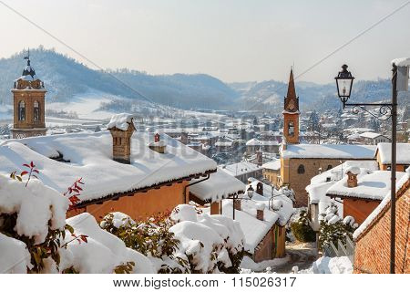 Roofs and churches covered with white snow in small town of Corneliano d'Alba in Piedmont, Northern Italy.